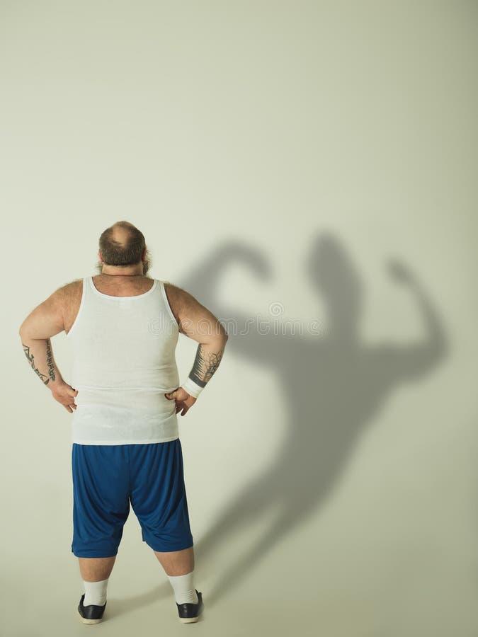 Hombre gordo que sueña con figura muscular del ajuste imagenes de archivo