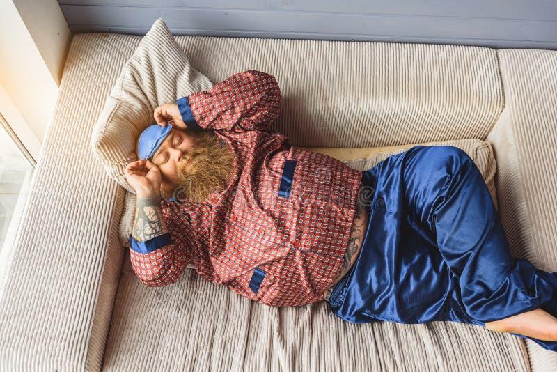 Hombre gordo tranquilo que tiene siesta en casa foto de archivo
