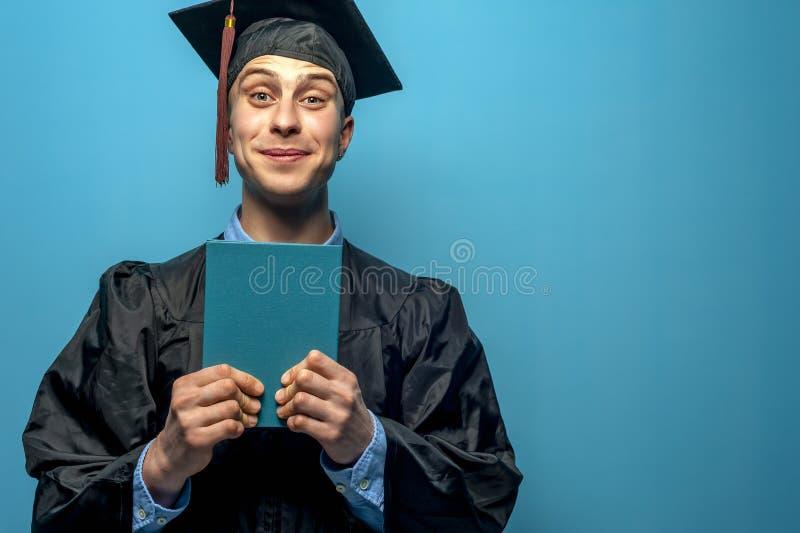 Hombre graduado alegre feliz que sostiene el diploma azul imagenes de archivo