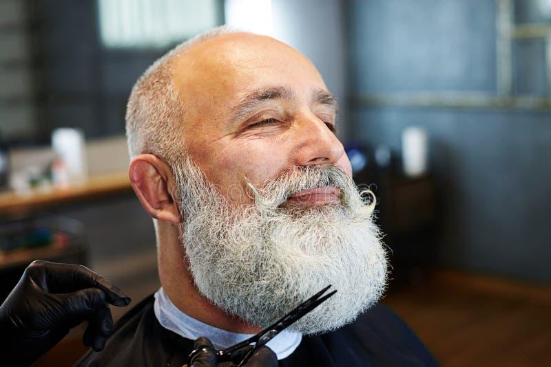 hombre Gris-cabelludo en peluquería de caballeros imagen de archivo