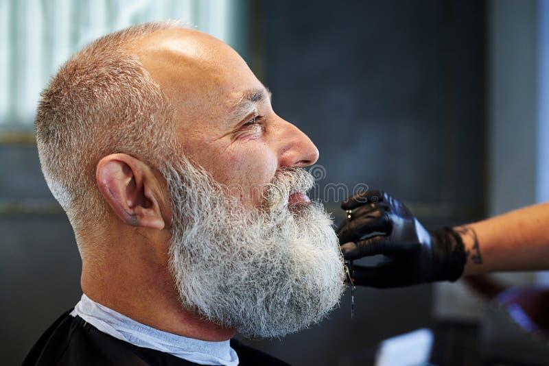 Hombre gris-cabelludo sonriente en peluquería de caballeros fotografía de archivo libre de regalías
