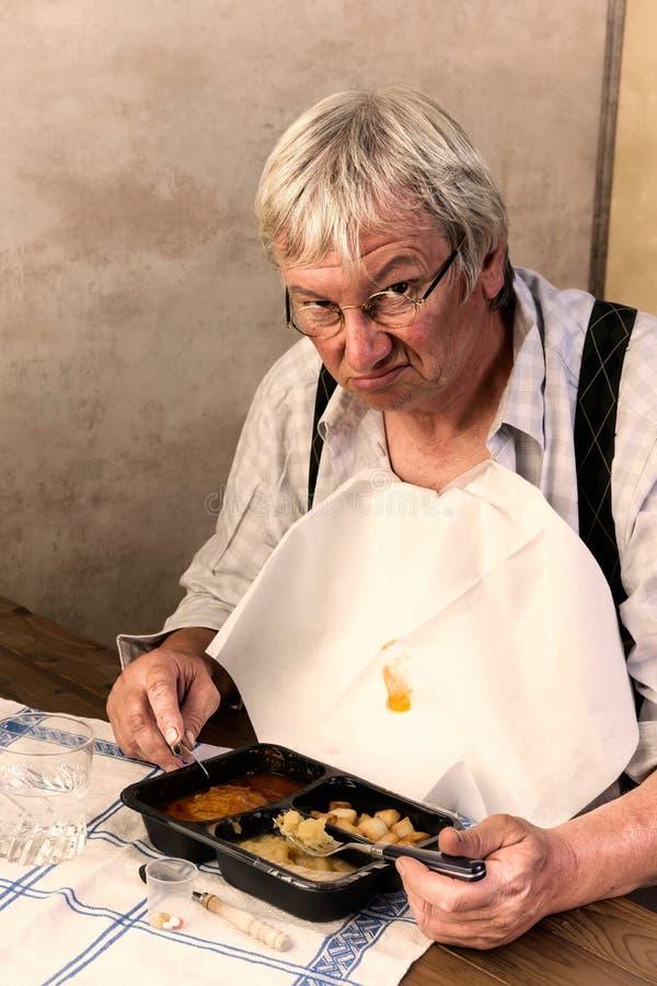 Hombre gruñón con la cena de TV fotos de archivo libres de regalías