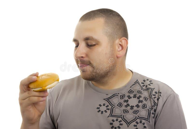 Hombre hambriento con la hamburguesa. imagen de archivo