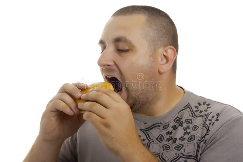 Hombre hambriento con la hamburguesa. imagen de archivo libre de regalías