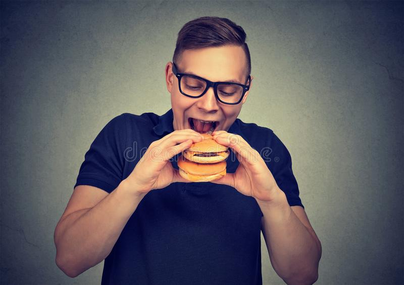 Hombre hambriento que come la hamburguesa doble imagenes de archivo