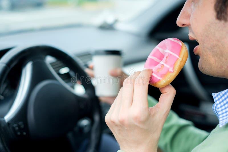 Hombre hambriento que conduce su coche mientras que come la comida en el tráfico fotos de archivo