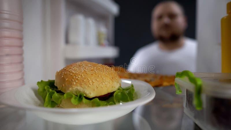 Hombre hambriento que mira la hamburguesa en el refrigerador, tentación de comer la comida rápida, fracaso de la dieta fotos de archivo