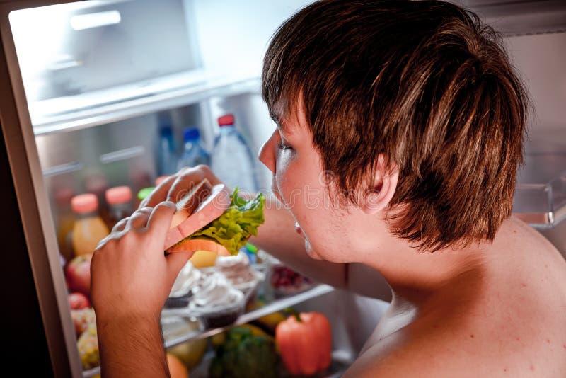 Hombre hambriento que sostiene un bocadillo en sus manos y situación al lado de fotografía de archivo