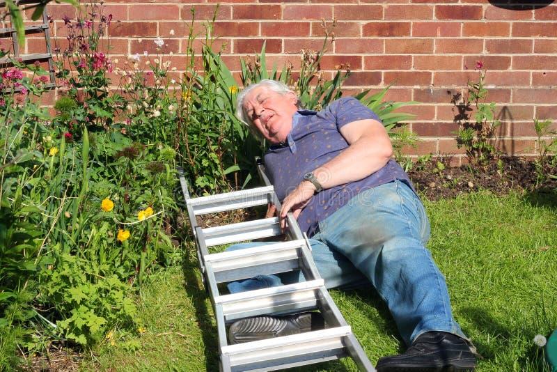 Hombre herido después de caer de una escalera. fotografía de archivo libre de regalías