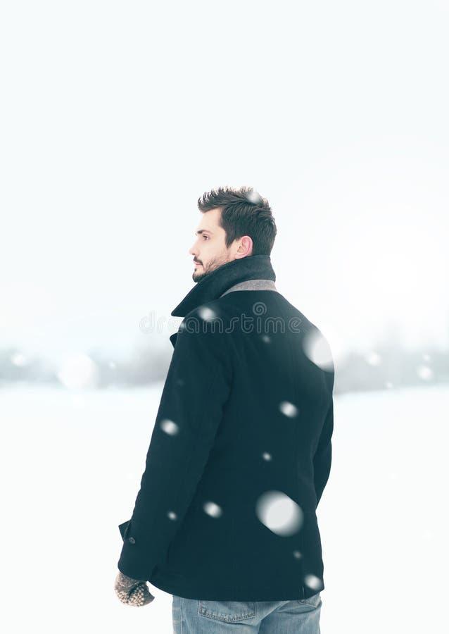 Hombre hermoso al aire libre que se coloca en la ventisca del invierno fotos de archivo