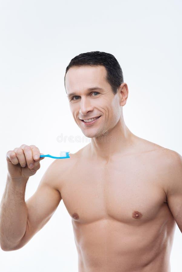 Hombre hermoso alegre que cepilla sus dientes fotos de archivo
