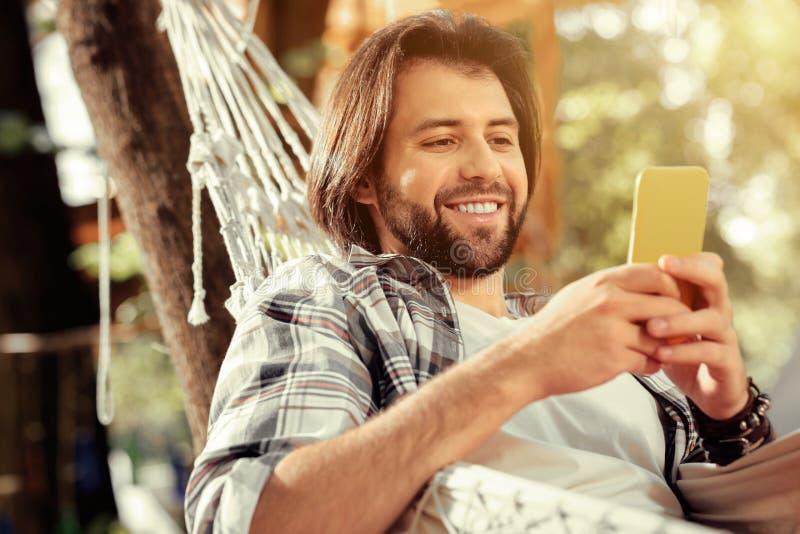 Hombre hermoso alegre que mira su pantalla del smartphone fotografía de archivo
