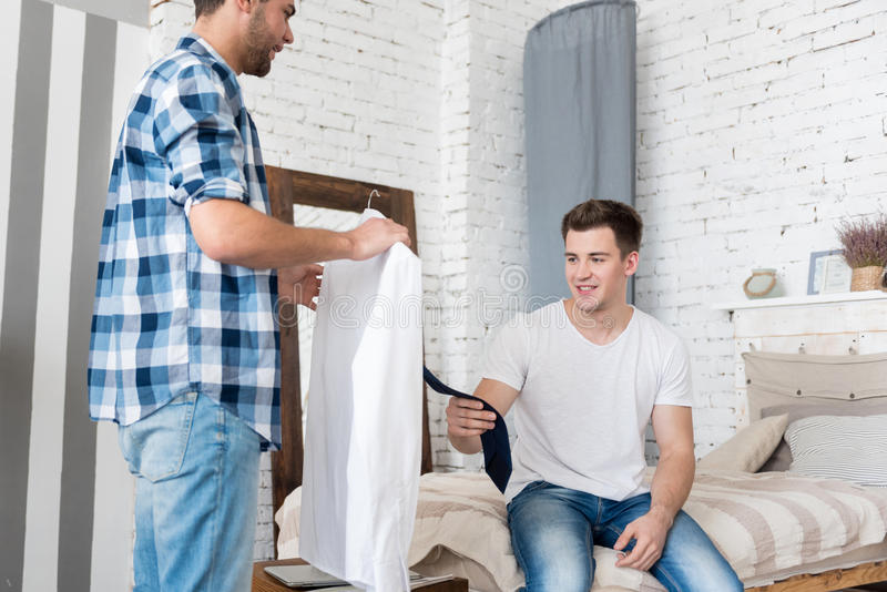 Hombre hermoso alegre que muestra un lazo a su novio foto de archivo