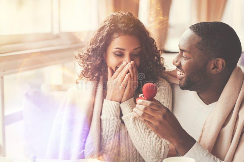 Hombre hermoso alegre que propone a su novia foto de archivo libre de regalías