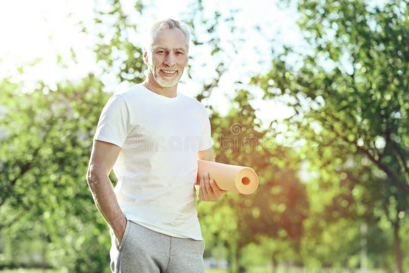 Hombre hermoso alegre que se coloca con una estera de la yoga fotos de archivo libres de regalías