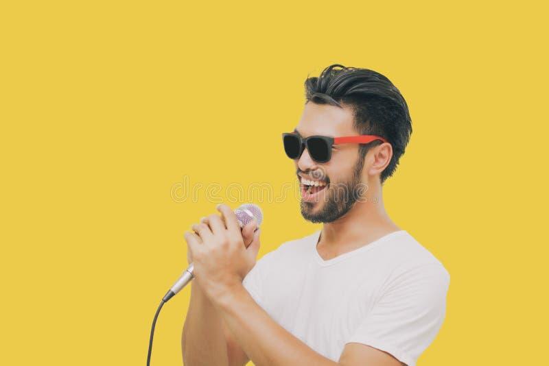 Hombre hermoso asiático con un bigote, sonriendo y cantando al micrófono aislado en fondo amarillo imagen de archivo