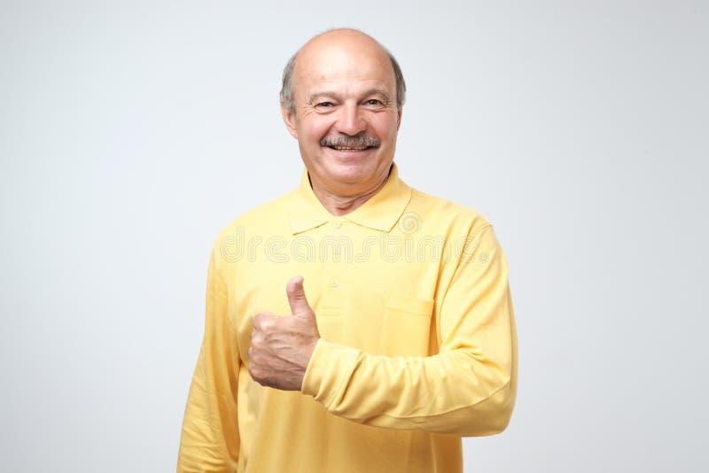Hombre hermoso, calvo con su pulgar para arriba en la muestra del optimismo en el fondo blanco foto de archivo libre de regalías
