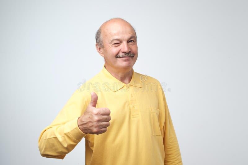 Hombre hermoso, calvo con su pulgar para arriba en la muestra del optimismo en el fondo blanco imagen de archivo