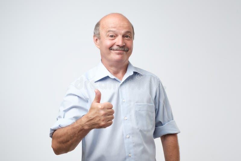 Hombre hermoso, calvo con su pulgar para arriba en la muestra del optimismo en el fondo blanco fotografía de archivo