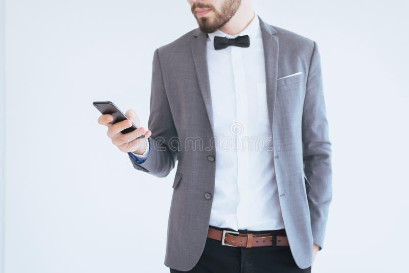 Hombre hermoso con barbudo en smoking formal y el traje que sostienen el teléfono elegante en el fondo blanco imágenes de archivo libres de regalías