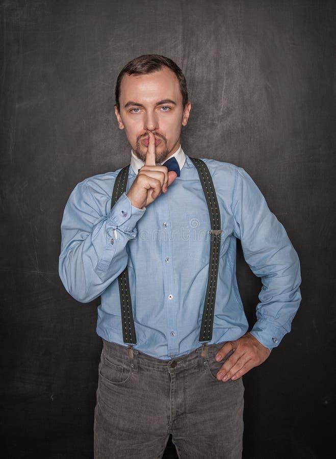 Hombre hermoso con el finger en los labios en la pizarra imágenes de archivo libres de regalías
