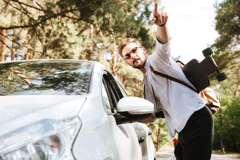 Hombre hermoso con el monopatín al aire libre que coloca señalar cercano del coche foto de archivo