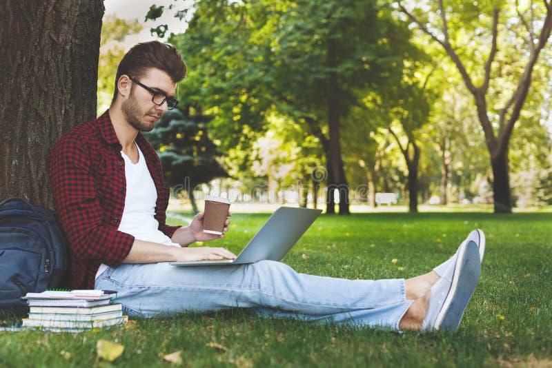 Hombre hermoso con el ordenador portátil y el café al aire libre fotografía de archivo libre de regalías