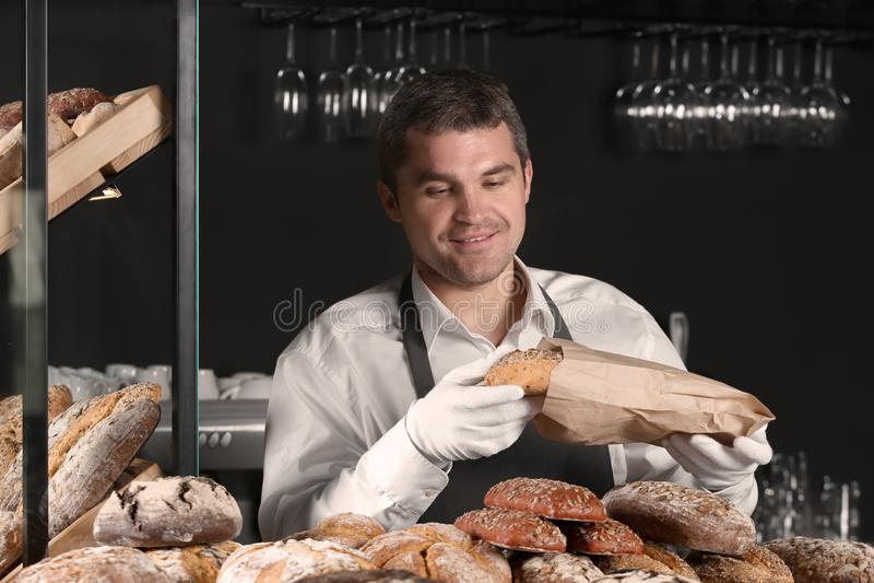 Hombre hermoso con el pan recientemente cocido que trabaja en tienda de la panadería fotografía de archivo