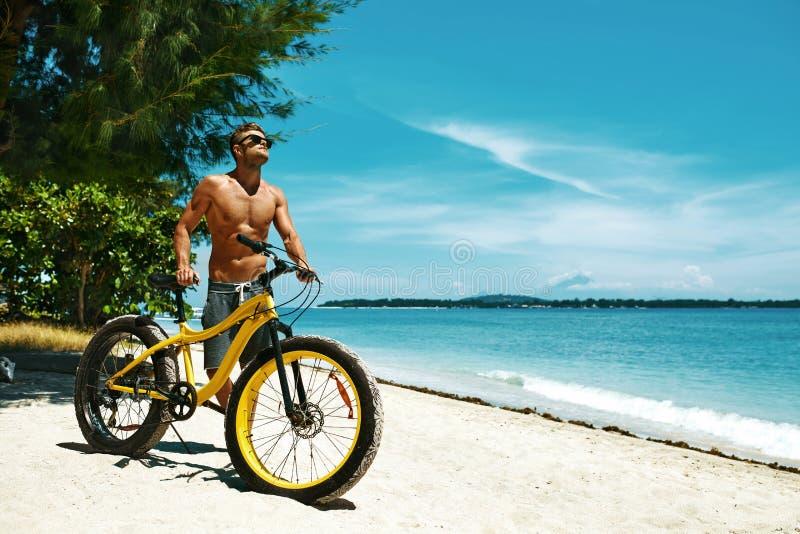 Hombre hermoso con la bici Sun que broncea en la playa Vacaciones de verano imagen de archivo
