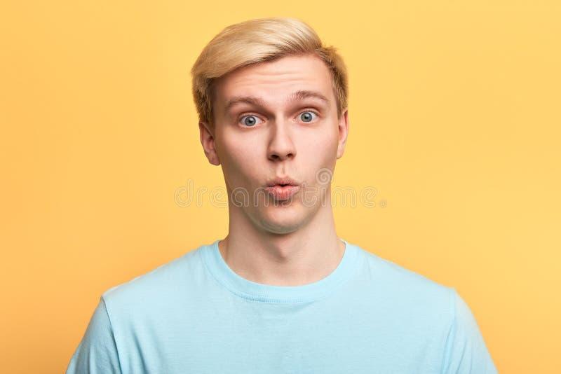 Hombre hermoso con la expresión facial divertida que intenta silbar foto de archivo libre de regalías