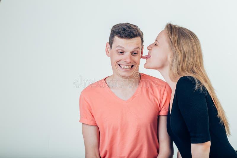 Hombre hermoso con la mujer atractiva hermosa que lame la mejilla del hombre fotografía de archivo
