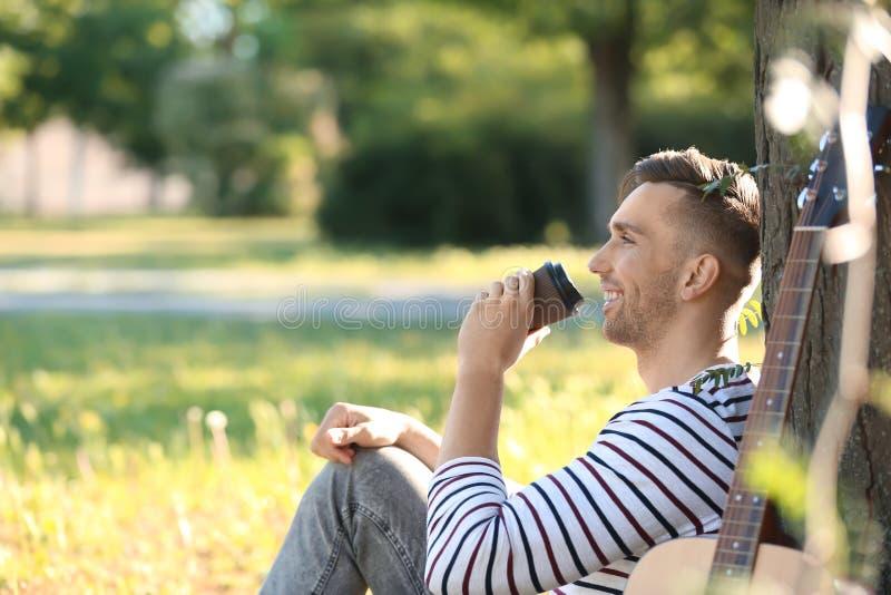 Hombre hermoso con la taza de café y de guitarra que descansan en parque foto de archivo