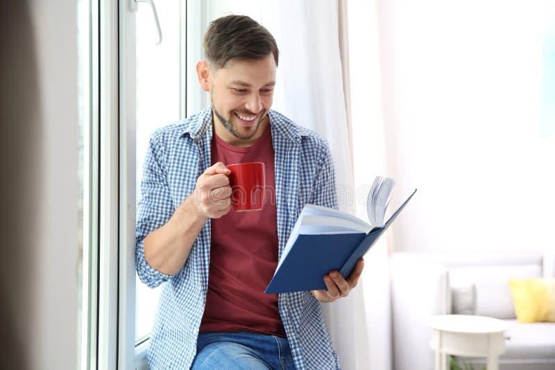Hombre hermoso con la taza de libro de lectura del café imagen de archivo