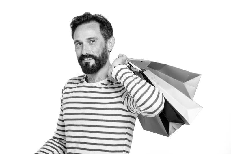 Hombre hermoso con las bolsas de papel aisladas en blanco Hombre en bolsos de compras de la camiseta de la marina de guerra que l imagen de archivo