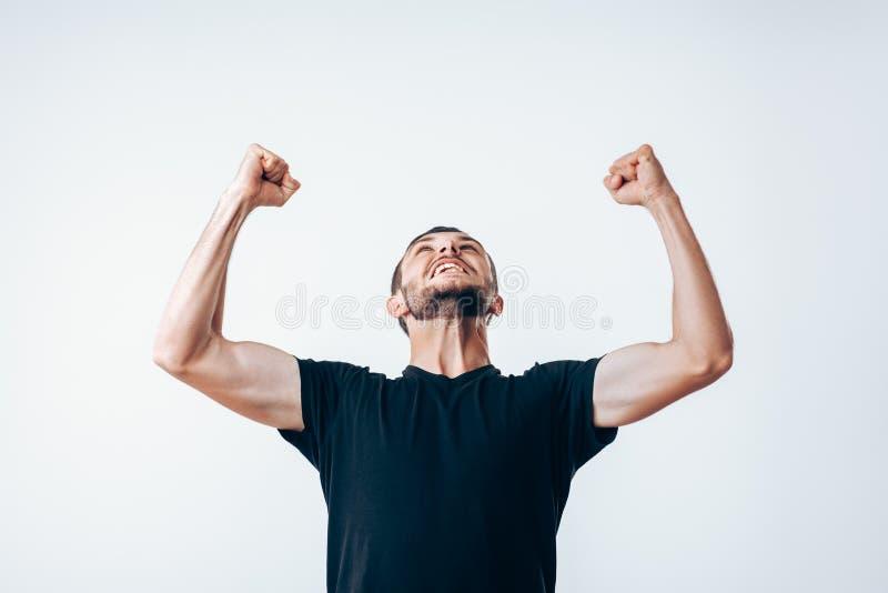 Hombre hermoso con los brazos para arriba que celebra éxito imagen de archivo libre de regalías