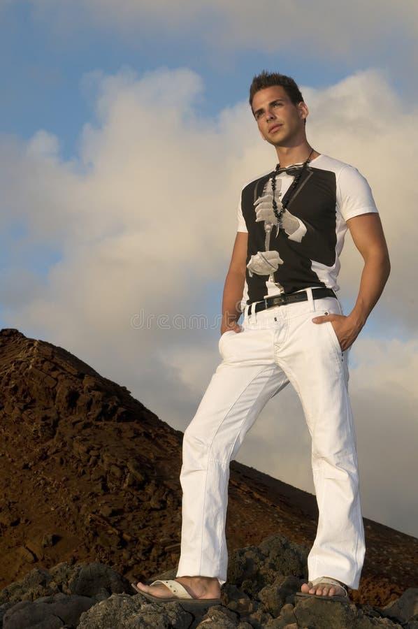 Hombre hermoso con los pantalones blancos foto de archivo