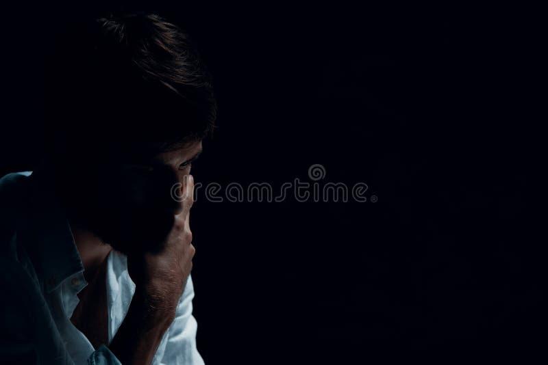 Hombre hermoso con problemas, espacio de la copia en el fondo negro foto de archivo