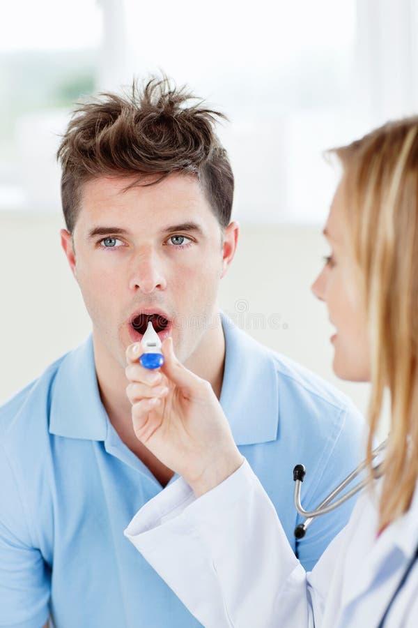 Hombre hermoso con su doctor que toma temperatura imagen de archivo