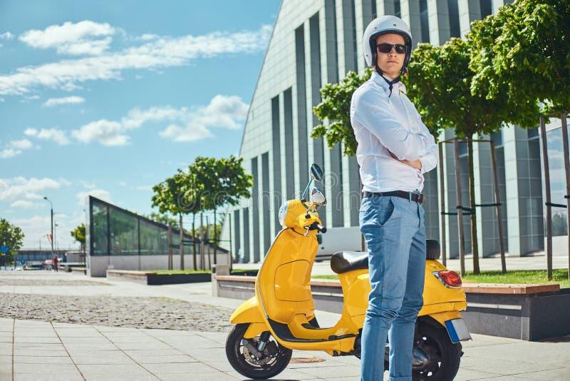 Hombre hermoso confiado con corte de pelo elegante en una camisa blanca, vaqueros, gafas de sol y el casco del motocycle que se c foto de archivo