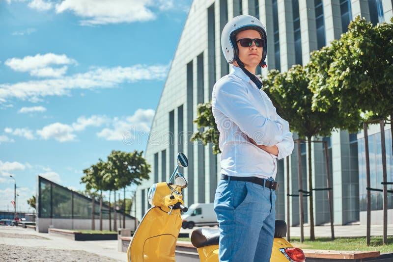 Hombre hermoso confiado con corte de pelo elegante en una camisa blanca, vaqueros, gafas de sol y el casco del motocycle que se c fotografía de archivo libre de regalías