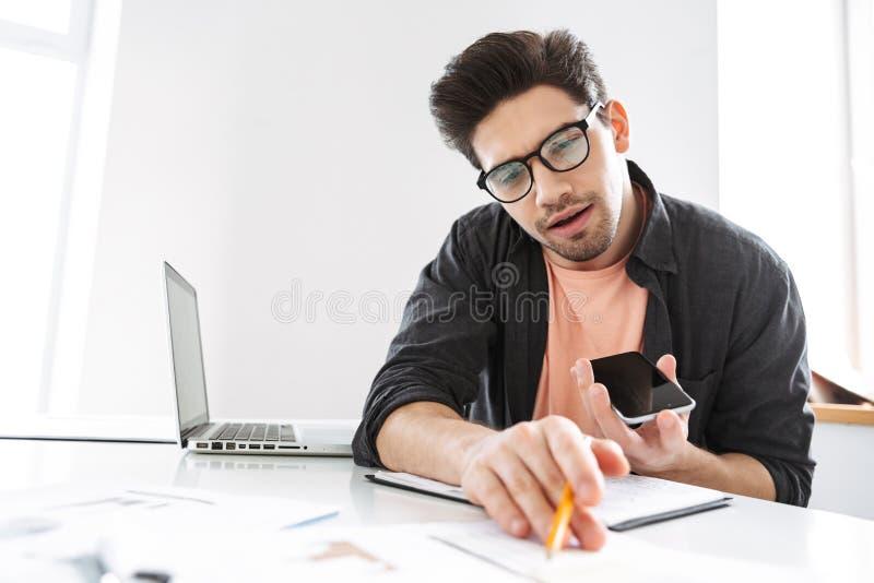 Hombre hermoso contento en lentes que habla smartphone y trabajando imagenes de archivo