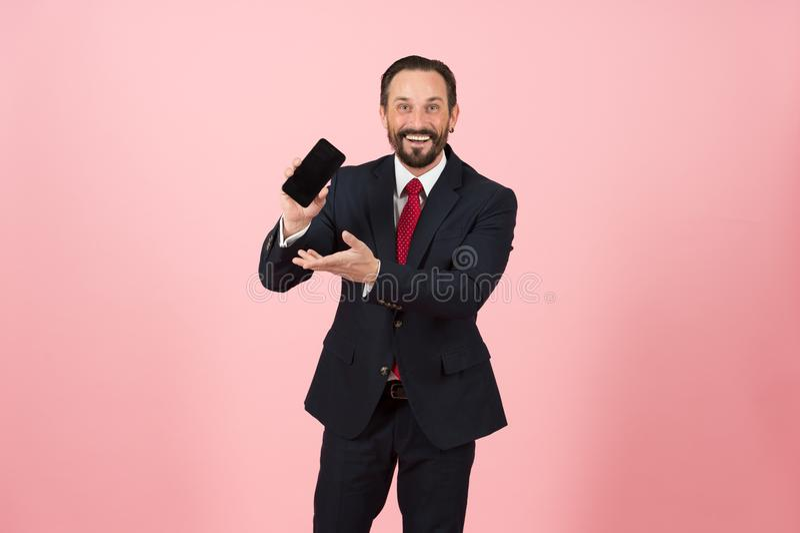 Hombre hermoso de las ventas en el traje y el lazo rojo que muestran su teléfono a la cámara y que señalan a ella Haga negocio fe fotos de archivo