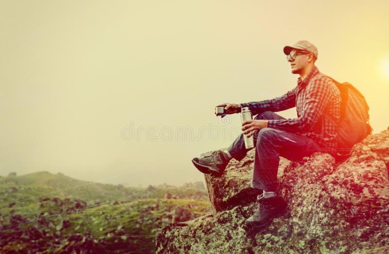 Hombre hermoso del caminante que se sienta en el top y que sostiene el termo en su mano, entonada e imagen de los rasguños imagen de archivo libre de regalías