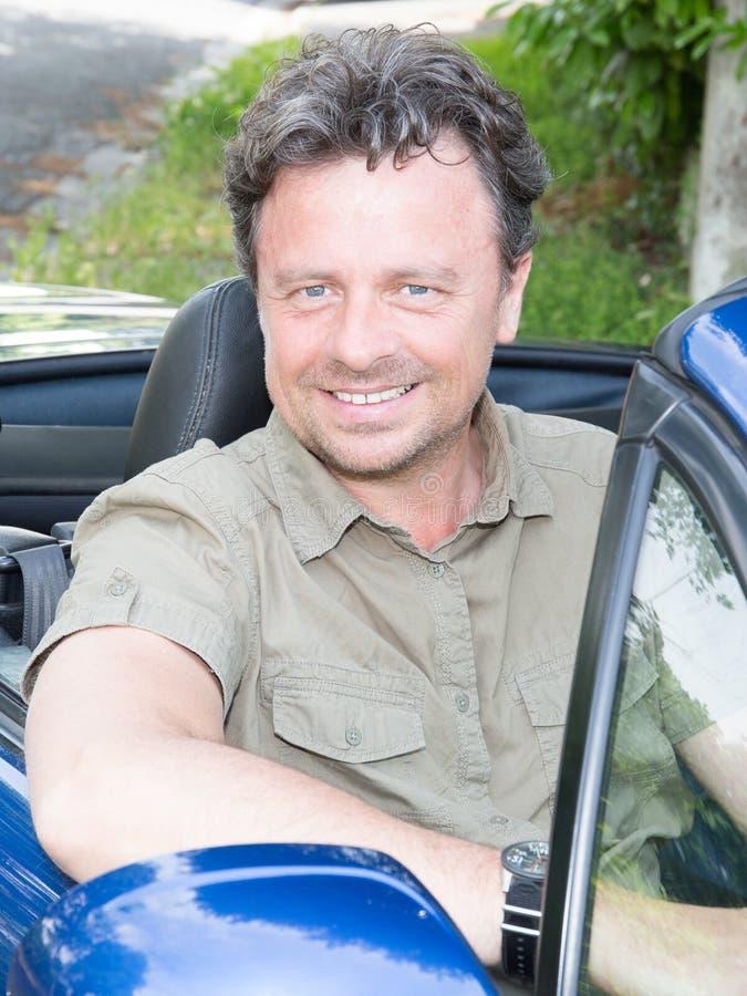 Hombre hermoso del dueño que se sienta en su coche nuevamente comprado del cabriolé que mira hacia fuera la sonrisa de la ventana foto de archivo libre de regalías