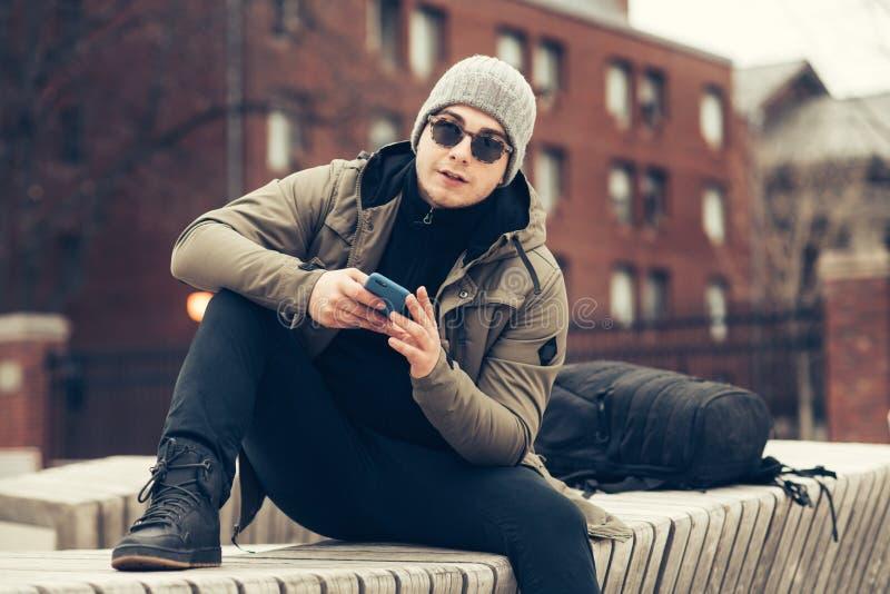 Hombre hermoso del estudiante que manda un SMS en el teléfono celular que se sienta en el banco que lleva la ropa casual imagenes de archivo