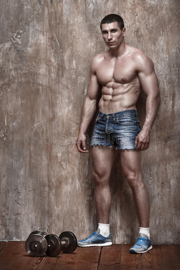 Hombre hermoso del músculo con pesas de gimnasia en fondo de la pared imagenes de archivo