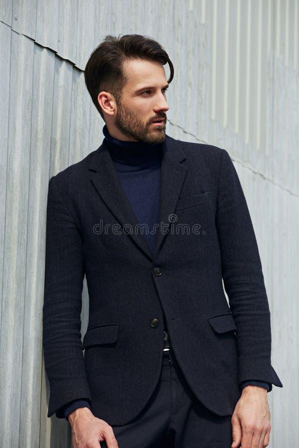 Hombre hermoso del negocio del estilo de la barba de la moda que presenta en ropa del estilo en fondo del aire libre de la pared  fotos de archivo