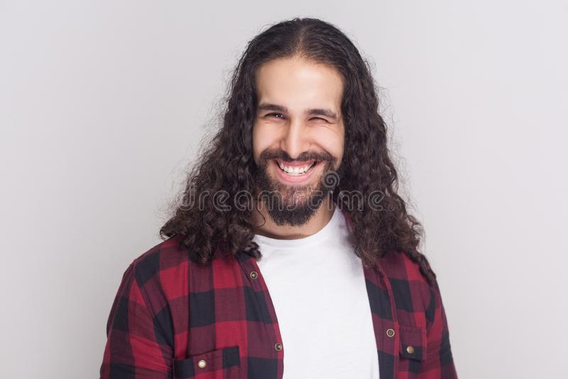 Hombre hermoso divertido con la barba y pelo rizado largo negro en casua imagenes de archivo