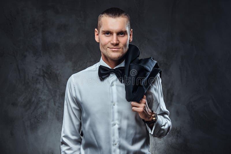 Hombre hermoso elegante vestido en la camisa blanca y la corbata de lazo que presentan para una cámara con la chaqueta en el homb fotos de archivo libres de regalías
