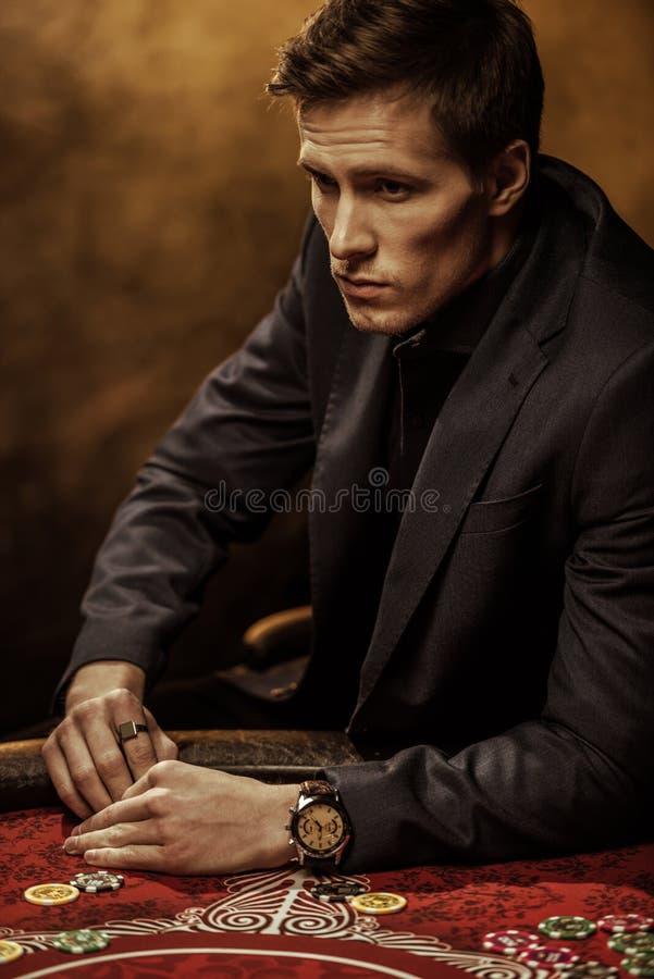 Hombre hermoso en el traje que se sienta en la tabla del póker y que mira lejos imagen de archivo